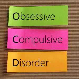 obsessive compulsive disorder on three different coloured labels in bold OCD