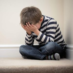 an upset boy with his head is his hands due to CSE