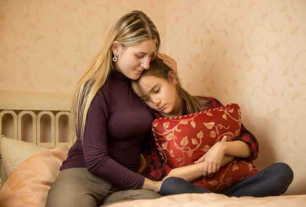 a mother hugging her sad daughter on bed as daughter hugs pillow because of FGM