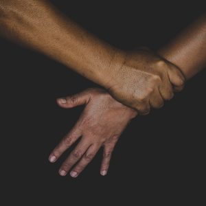 aggressive hand hold the arm of another with black background to signify HBV