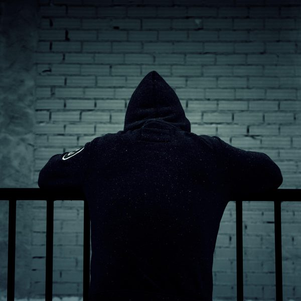 a person with a black hoodie leaning over a railing fence involved in gangs