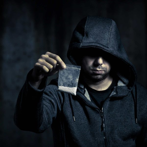 a hooded man holding drugs to signify county lines