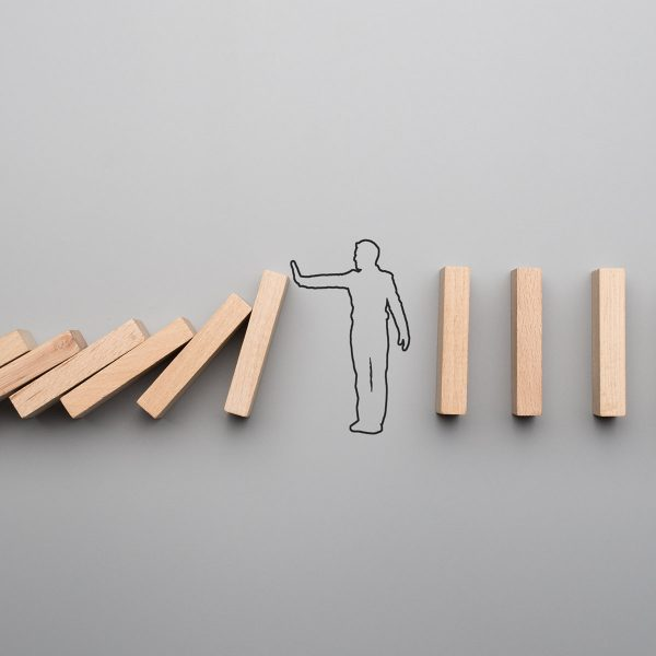stickman holding up wooden block to signify stopping radicalisation