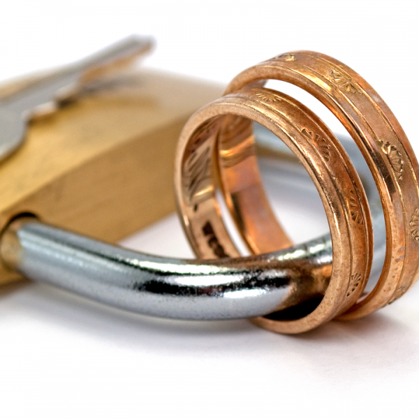 two gold rings intertwined by a padlock to signify forced marriage, FGM & HBV