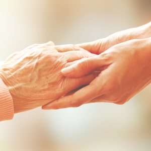 elderly hand being held by a young hand to signify care settings