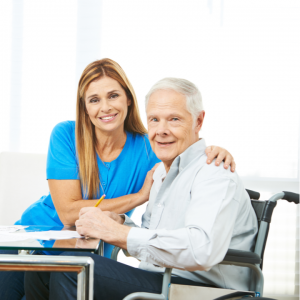 a female with their arm over the shoulder of an elderly man in a wheelchair in a care setting