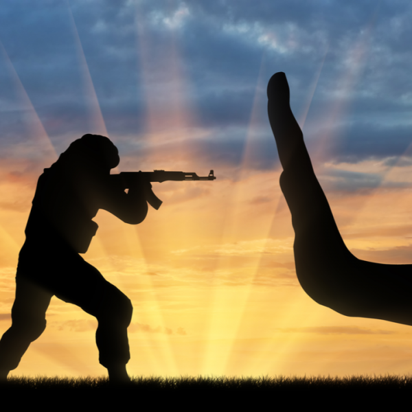 silhouette of a man with a gun and a big hand telling him to stop his extremism