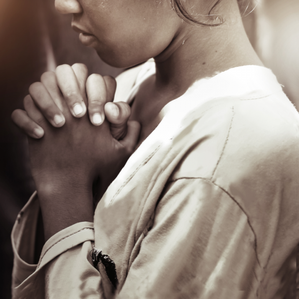 a black and white picture of a young girl praying to her chosen faith.
