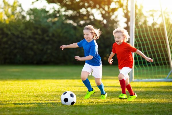 two-chldren-in-red-and-blue-tops-playing-football. introduction