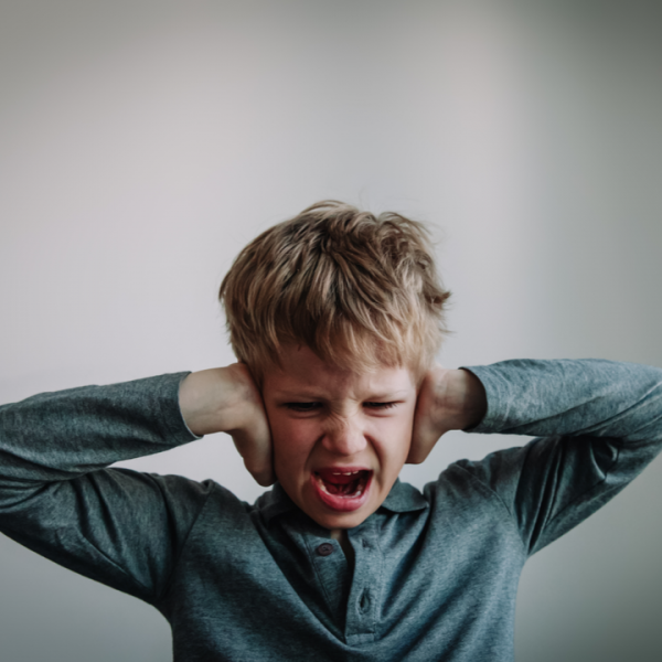 young boy screaming with hands over ears needing positive handling