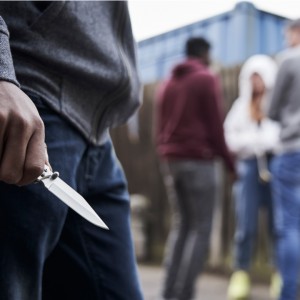 someone involved with gangs holding a knife