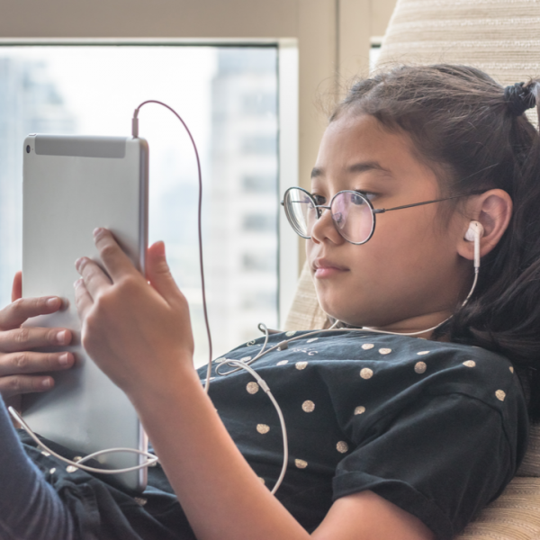 a young girl on a tablet with earphones highlighting online safety