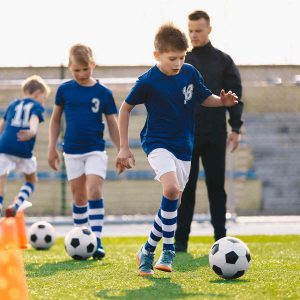 young children in blue and white kit with a coach behind them playing football at a sports club